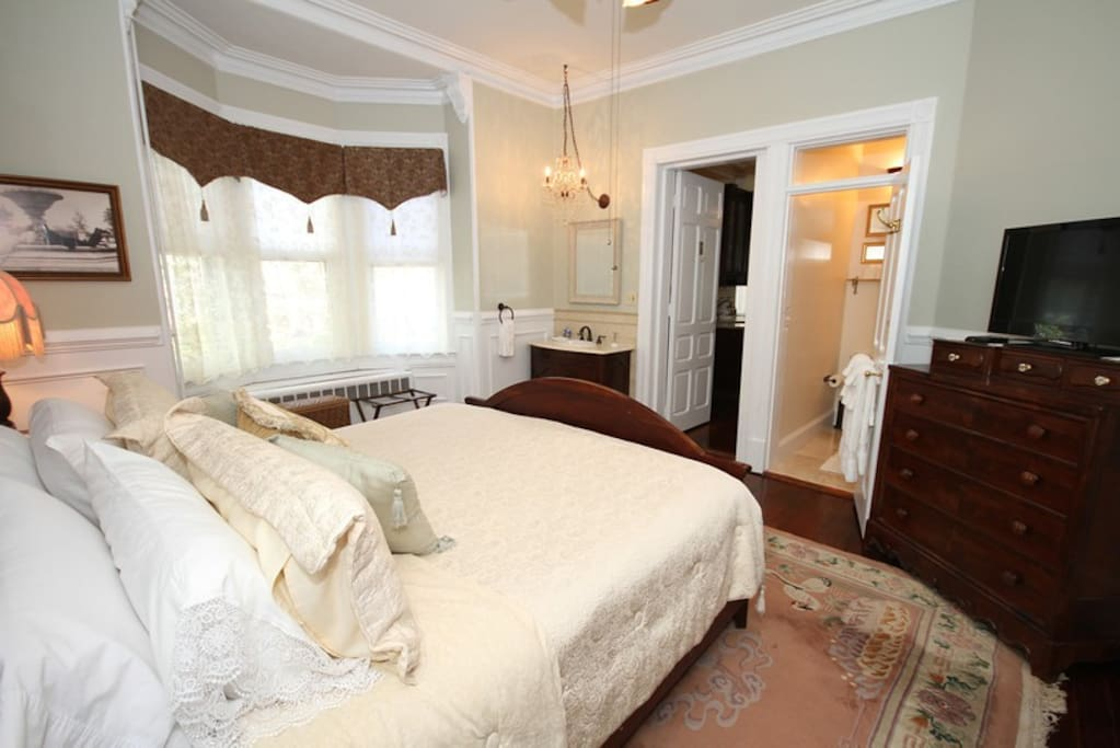 Spacious bedroom with high ceiling and charming vanity area, TV