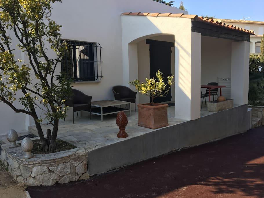 Terrasse couverte avec table et chaises et salon extérieur