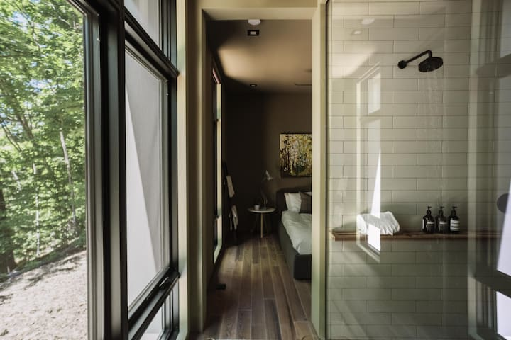 Master bed and bath with floor to ceiling glass and windows