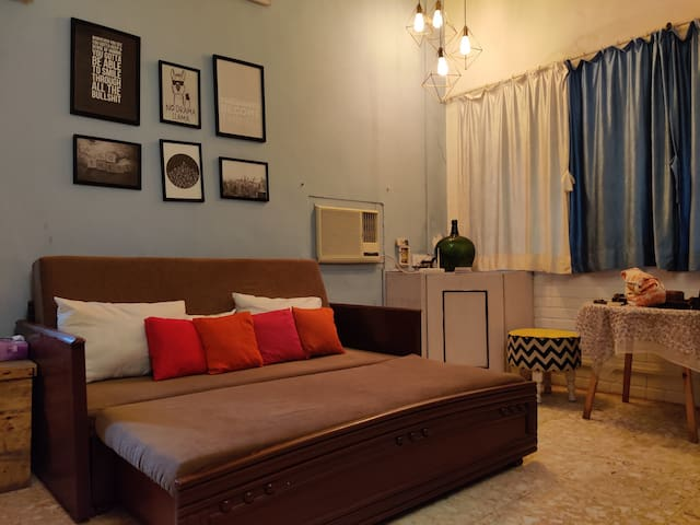 This is the other side of the bedroom. We prefer mood lighting in the evenings after a long day. The right side has a table with two seatings where you can work or eat or have a cup of coffee perhaps.  There is an AC/ Wifi near the vase & writing pad