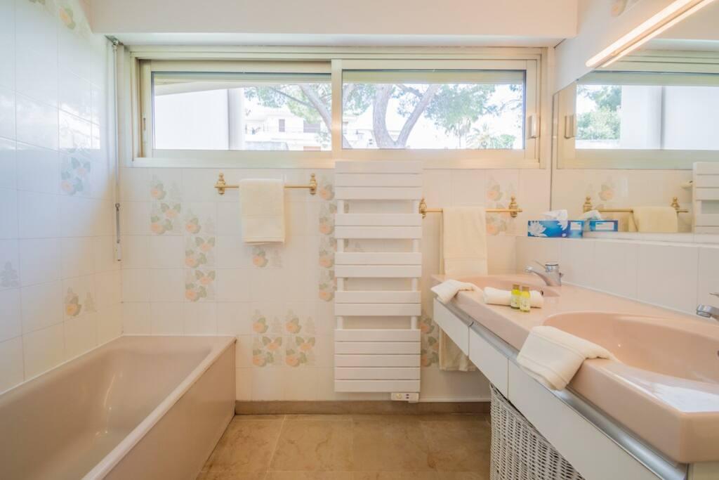 Full bathroom with bathtub, double sink, towel warmer