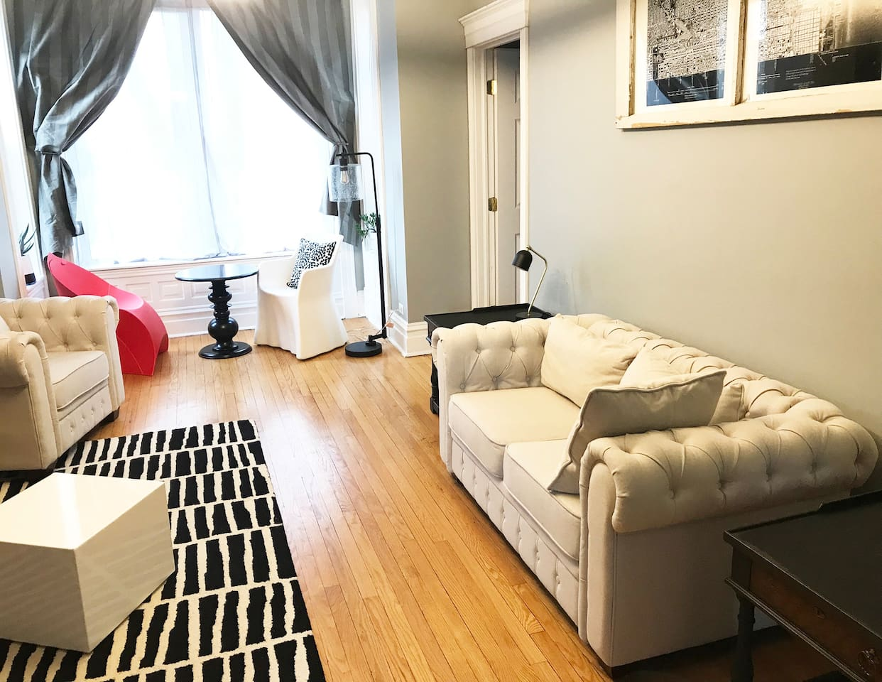 Bright, sun filled comfortable living room  with beautiful picture window to a quiet tree lined street.