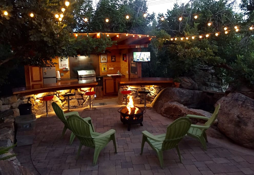 private grotto patio with fire pit, bar, grill, fridge, tv, waterfall, and market lights