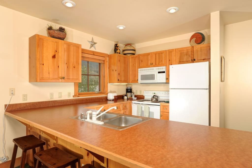 The fully-equipped kitchen features lots of counter space and a breakfast bar