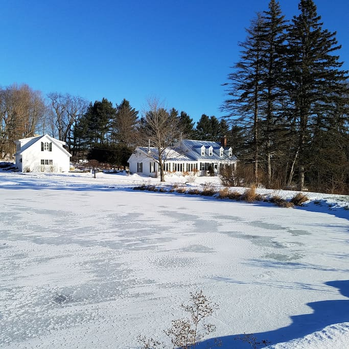 Guest house and Main house across large frozen pond.