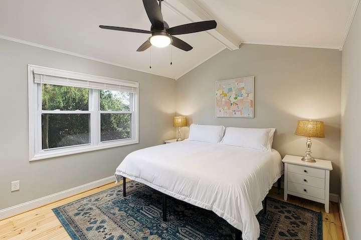 Private bedroom with king sized bed, 2 closets, 2 night stands and a dresser with mirror.