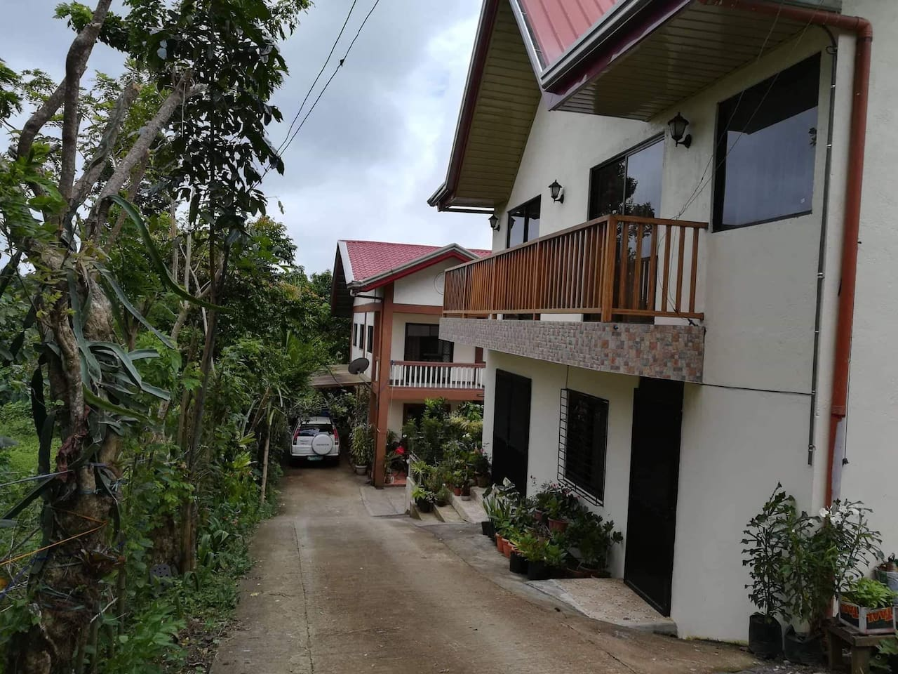 "This is the view of the guest house. Please be advised that all other photos are from the second floor of the house, hence the balcony. The first floor has a common area, one bedroom, and a bathroom. No one resides there but it will be available for rent at an additional cost if guests are more than 12. Parking is available for guests.  The house below is the owner's house. Ma. Paz Sunga, ""Nanay Paz"" or ""Tita Paz"", is the owner of Marvigrace Enterprises. It is a company that started the souvenir Tagaytay shirts you see all over Tagaytay. Walking distance from the house is where they do all those shirts and uniforms, we also have a store so you can buy souvenir shirts at a lower cost! :)"