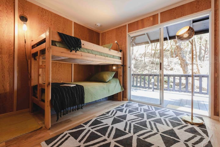 The main level bedroom is furnished with a twin bunk bed and another private deck with views.