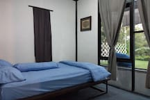 3rd bedroom with queen bed, and a view to green valley and citylight..