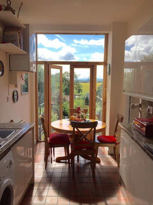 Sunny brand newly fitted kitchen with doors to garden and terrace