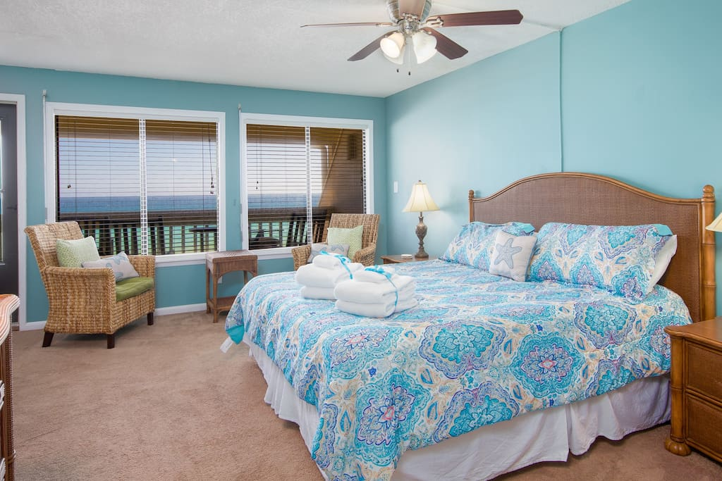 Gulf-Font King Master Bedroom features Coastal Decor, Carpet Throughout, Ceiling Fan, Tons of Natural Lighting, and a Sitting Area!