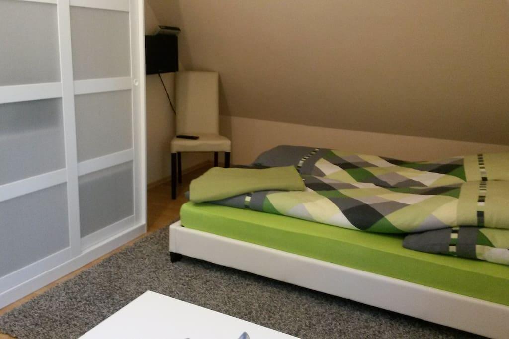 Das Doppelbett (160x200), der Schrank und der LED-Fernseher an der Wand