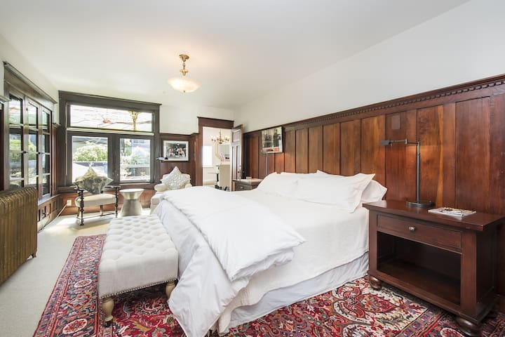 King Bed, wall-mount television, and reading nook by windows.