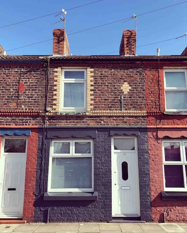 Front of the house. Opposite is a primary school. There is free on street parking. We are a couple of streets away from Birkenhead Park train station and Birkenhead Park is at the end of the road.