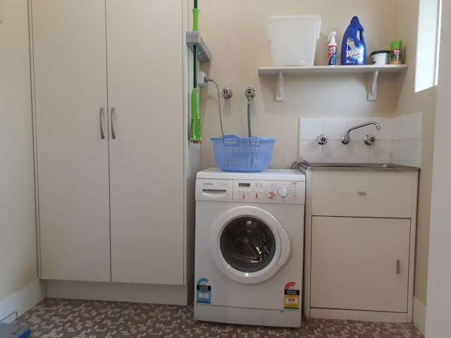 Laundry with washing machine, tumble dryer (not shown), iron and ironing board.