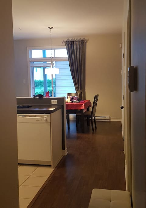 Intérieur depuis la porte d'entrée, la perspective montre la cuisine, la salle à manger et tout au fond, le petit patio. À droite se trouvent les 2 chambres et la salle de bain.