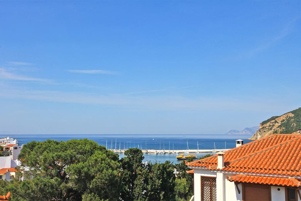 Panoramic view to town, harbour and neigbouring Alonnissos island from private covered balcony.