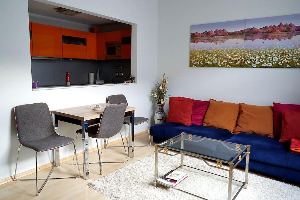 Helles Wohnzimmer mit halboffener Küche
