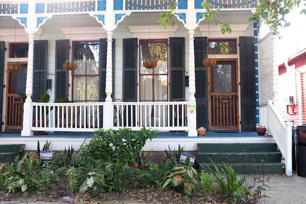 Beautiful updated front porch with lush front garden perfect for coffee in the morning and a sazerac at night.