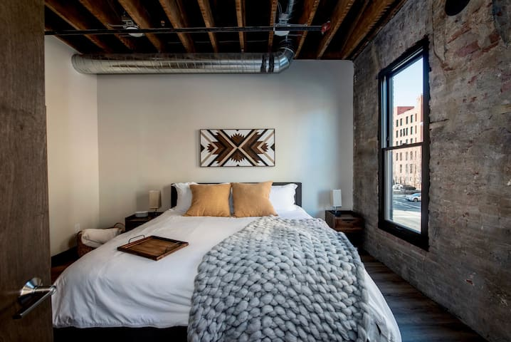 Master bedroom with King bed. Art featured by local artist CJ Morrison @roamingrootswoodworks