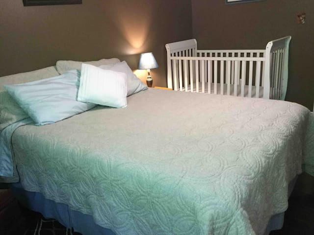 Bedroom with queen bed and crib