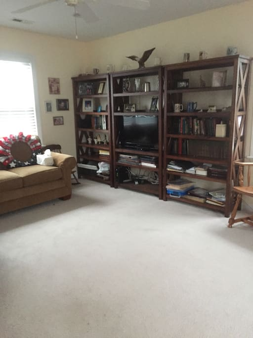 The spacious Hobby Room features a love seat and TV as well as a play table for children.