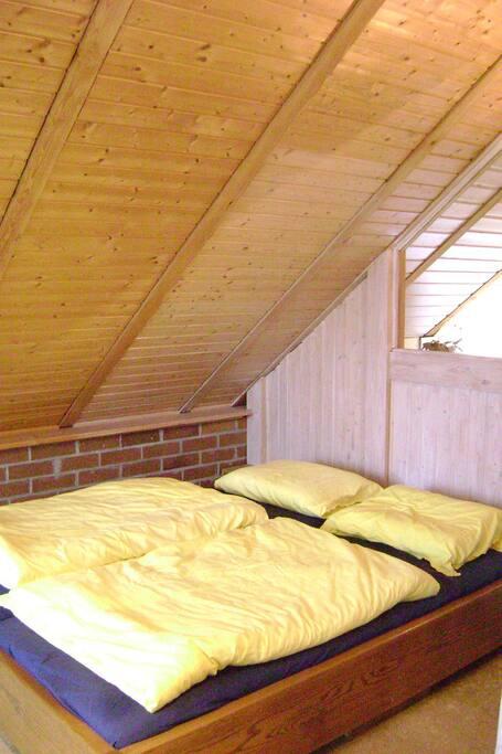Gemütliches Doppelbett unter der Schräge