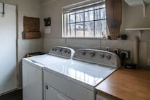 The utility room is the back entrance of the house closest to the available parking spot.  Located next to the bathroom and kitchen, it has a full-size washer and dryer, a cordless Dyson V10 vacuum, drying line, dishwasher, towels, and recycling bin.
