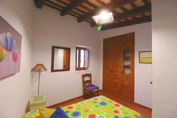 Habitación complementaria con cama y armario empotrado y escritorio.