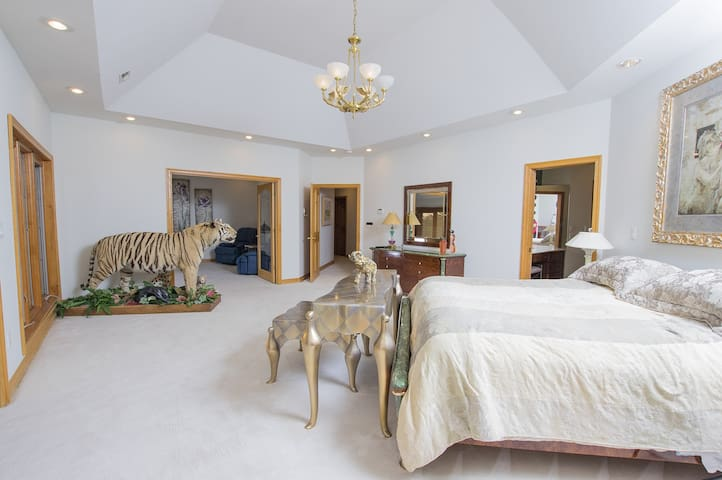 Master Bedroom with king bed, gas fireplace, sun room, tv room and large jetted tub
