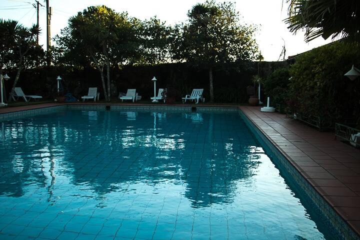 A casa fica do lado direito da piscina. Pode abrir a porta e dar um mergulho!