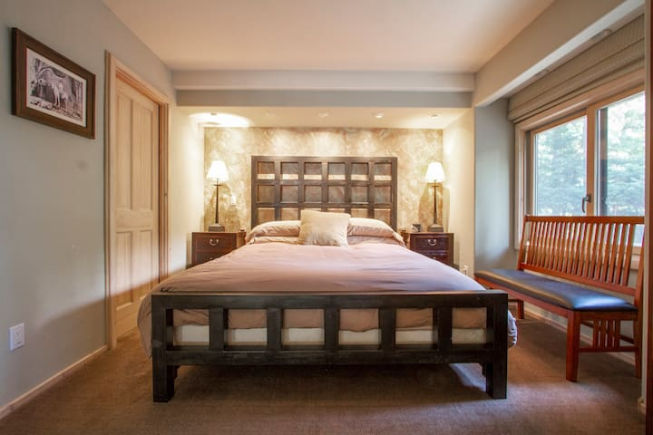 The master bedroom in the main house features a large king sized bed with a heavy steel frame.