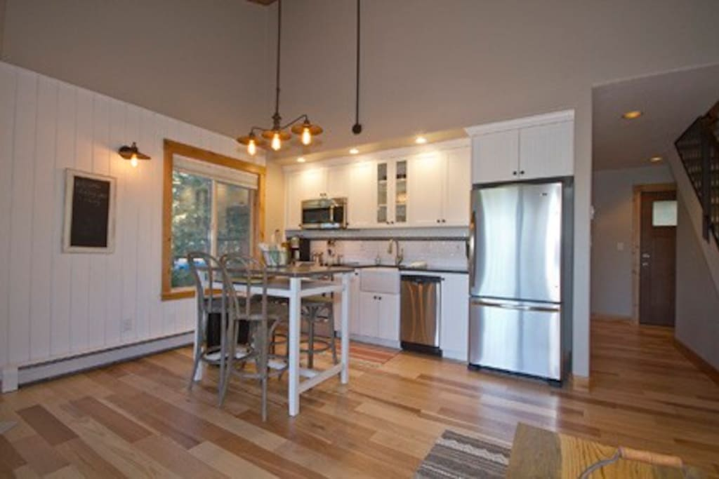 Fully equipped galley kitchen with granite slab counter tops and a stainless steel mobile work space