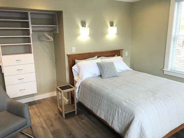 Front bedroom with queen bed and open closet.
