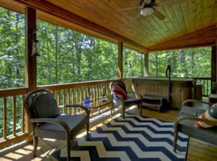 Back porch off the main room. Large hot tub private wooded area.
