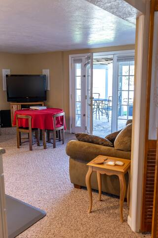 Living room/full kitchen has an eating area and seating area to watch the large flat screen TV.  French doors open to the private patio.