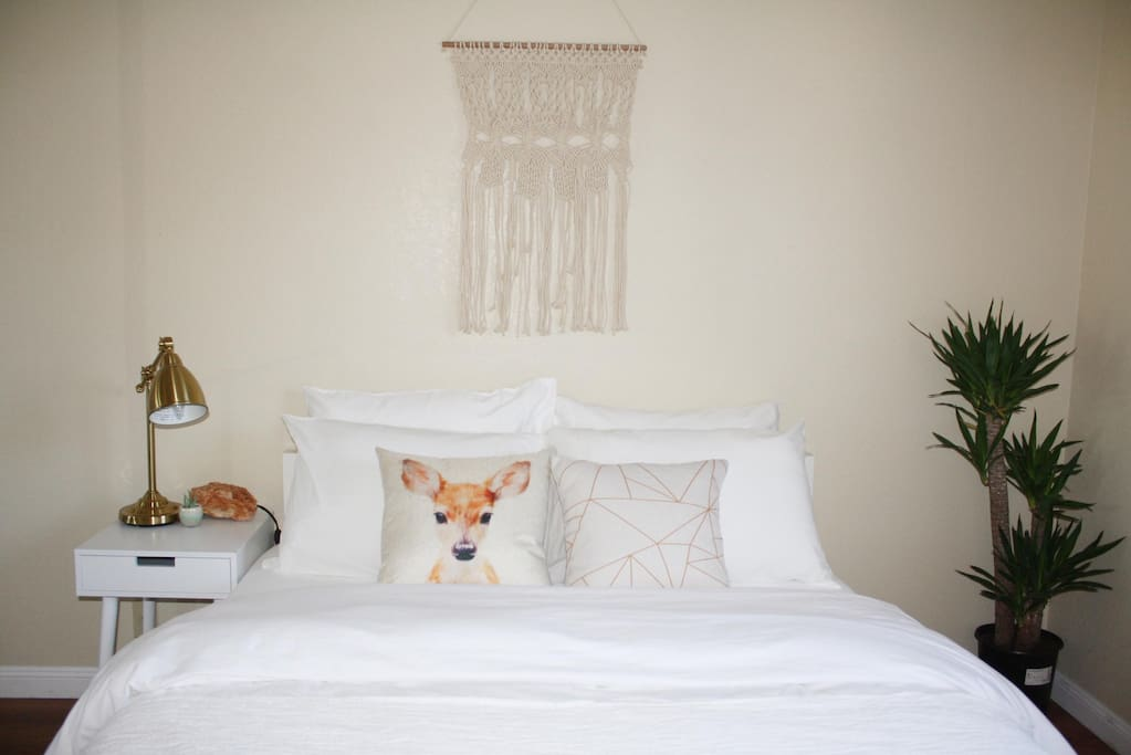 The room is beige with white furnishing and a touch of gold and green to achieve a clean modern look.