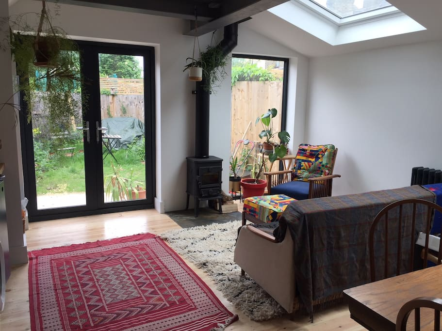 Kitchen, dining & living room, filled with light, rugs and plants, looking onto private garden