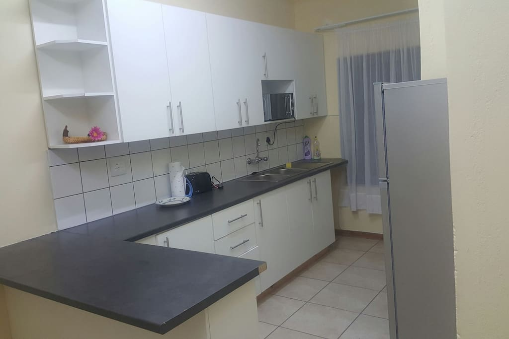 Spacious kitchen with stove, fridge, microwave, kettle, toaster and basic kitchen cutlery.