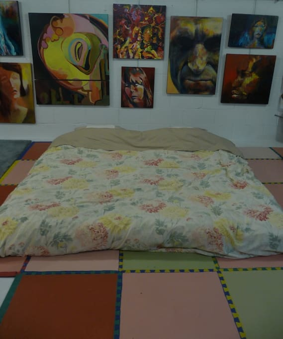 The bed, surrounded by art