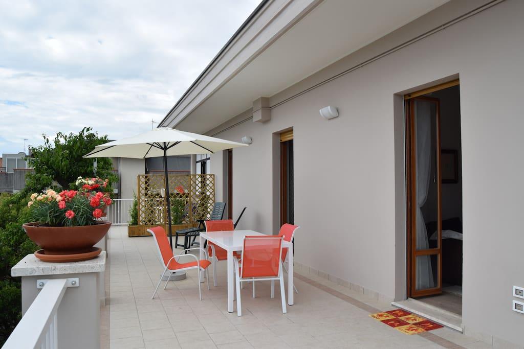 terrazzo con tavolo per 6 persone ed ombrellone