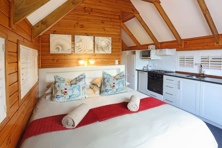 Double bedroom with a fully equipped self catering kitchen all in one room.  This cabin does not have a sea view.