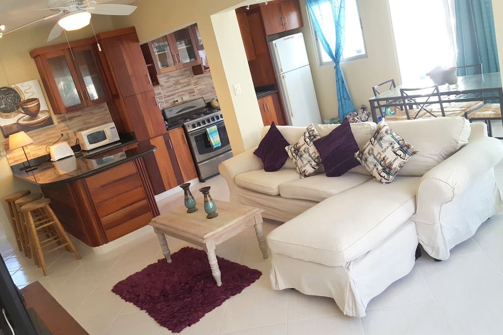 """Living room - large open plan living room with panoramic windows on 2 walls, 53"""" cable TV, sofas, dining table, kitchen"""