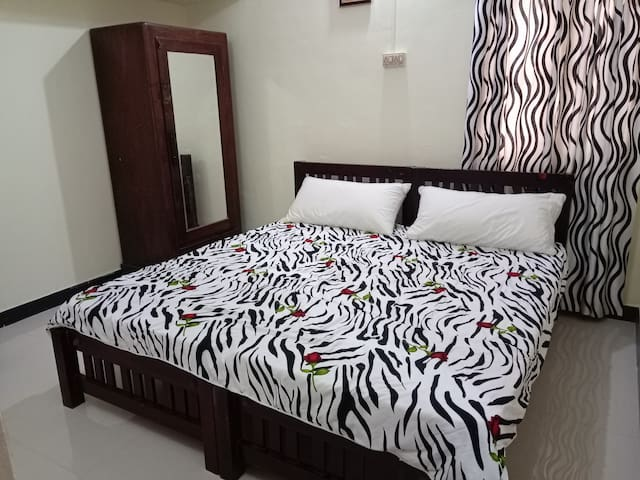 Bedroom 2 with attached bathroom, single beds are placed together if required to accommodate children.