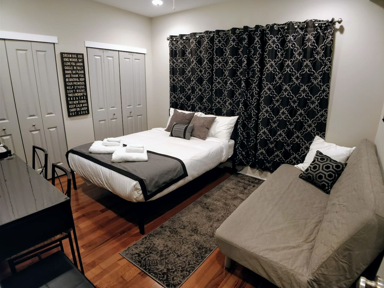 Spacious bedroom with queen size bed and sofa