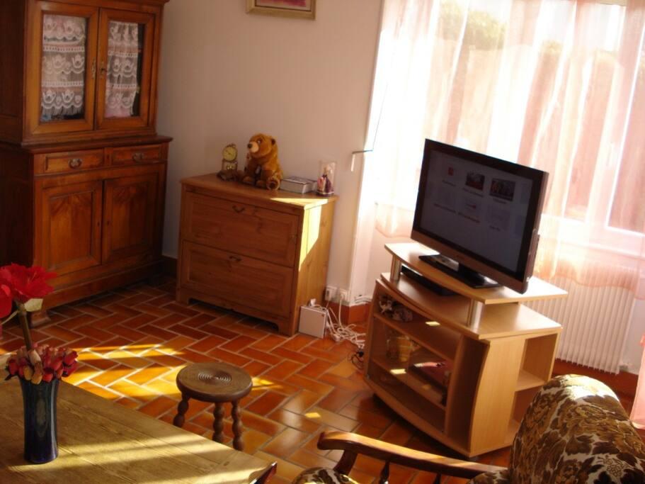 le salon possede un television , un canape et deux fauteuils