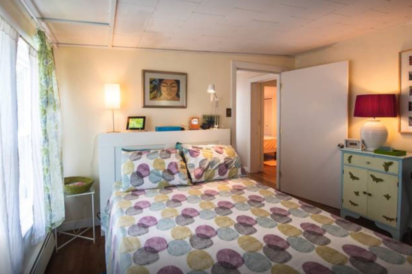 Private bedroom with full size bed, armoire, a/c window unit, two windows and luggage rack .