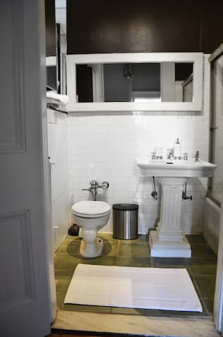 Bathroom with 100-year old subway tile and pedestal sink