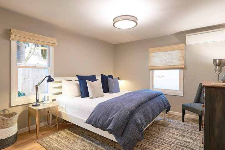 Large bedroom with king bed, luxe 100% cotton linens, duvet, tons of pillows, and both dresser and closet storage
