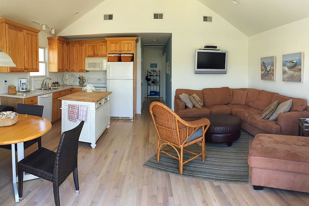 Common area with kitchen, dining, and living area. Stacked washer/dryer in hallway.
